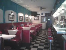 Long shotgun style dining room. Booths and stools just like it's supposed to be.